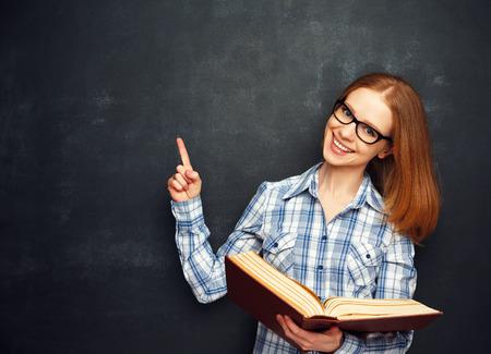 Chica estudiante feliz con gafas y un libro de la pizarra en blanco Foto de archivo - 42043979