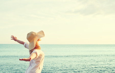 gente feliz: Mujer feliz de la belleza en el sombrero está de vuelta abrió las manos, se relaja y disfruta de la puesta de sol sobre el mar en la playa