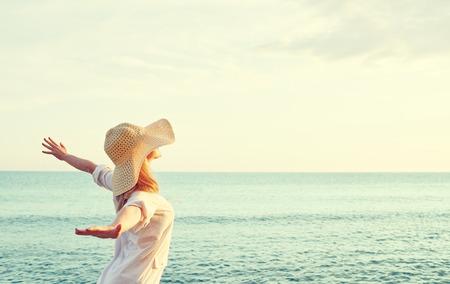 Mulher de beleza feliz no chapéu está de volta abriu as mãos, relaxa e aprecia o pôr do sol sobre o mar na praia Foto de archivo