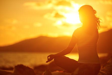 mujer meditando: yoga en la playa. mujer meditando en posición de loto en la playa al atardecer