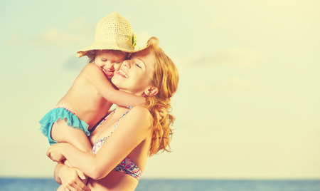 cielo y mar: familia feliz en la playa. madre y el bebé hija abrazo en el mar