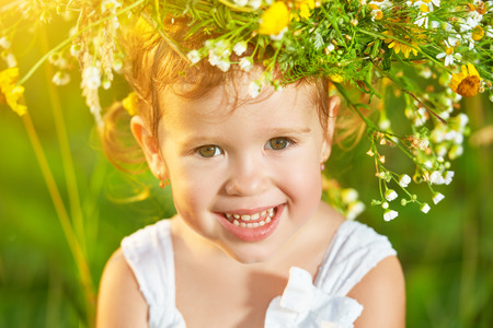 funny happy baby child girl in a wreath on the nature laughing in a meadow in summer