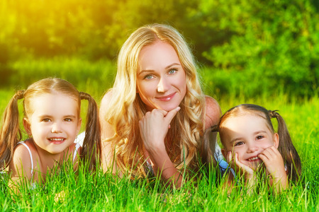 twin sister: happy family mother and children twin sisters on meadow in the summer on a green grass Stock Photo