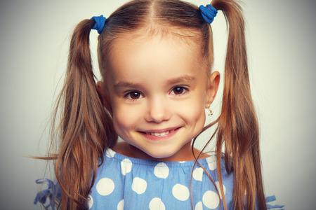 niños riendose: cara feliz niña graciosa en un vestido azul