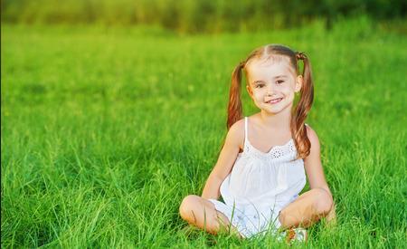 jolie petite fille: enfant heureux petite fille dans une robe blanche couch�e sur le Summer herbe