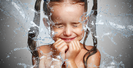 water spray: happy funny child girl in a spray of water droplets laughs