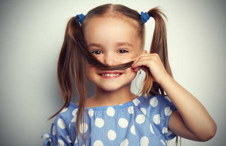 gelukkig gezicht grappig kind meisje in een blauwe jurk