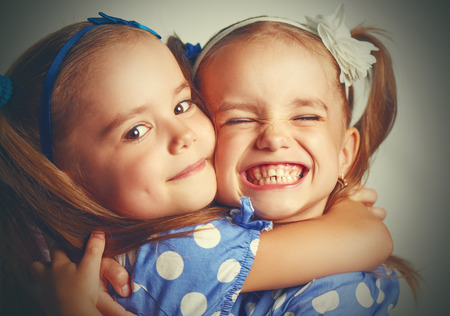 familia abrazo: Feliz gemelos divertidos chica hermanas abrazan y ríen Foto de archivo