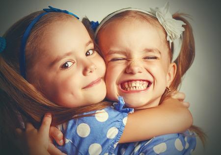 Gelukkig grappig meisje tweeling zusters knuffelen en lachen