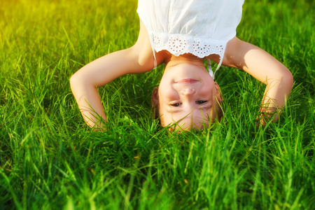 happy child girl standing upside down on his head on the grass in the summer