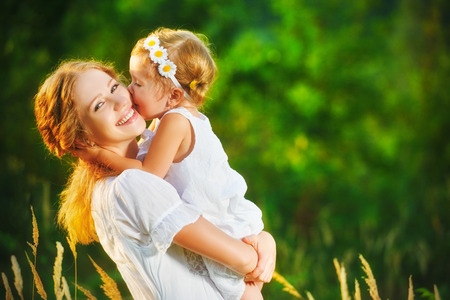 smiling mother: Happy family on a summer meadow. little girl child baby daughter hugging and kissing mother