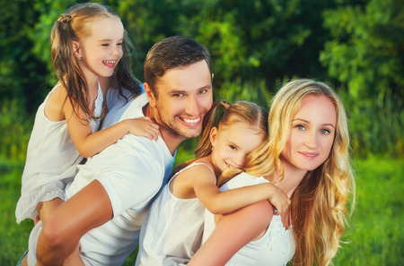 guy portrait: happy family on the nature of the summer, mother, father and children twin sisters