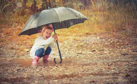 happy baby girl with an umbrella in the rain runs through the puddles playing on nature