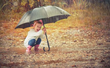 lluvia paraguas: niña feliz con un paraguas bajo la lluvia corre por los charcos que juegan en la naturaleza
