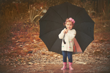 runs: happy baby girl with an umbrella in the rain runs through the puddles playing on nature