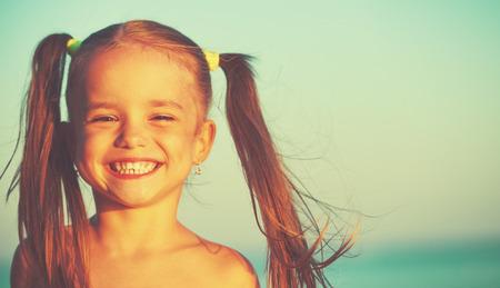 traje de bano: niña feliz en la playa junto al mar