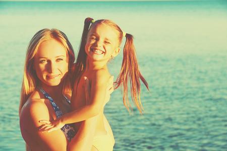 niñas jugando: familia feliz en la playa. madre y el bebé hija en el mar Foto de archivo