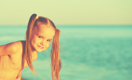happy girl child on the beach by the sea