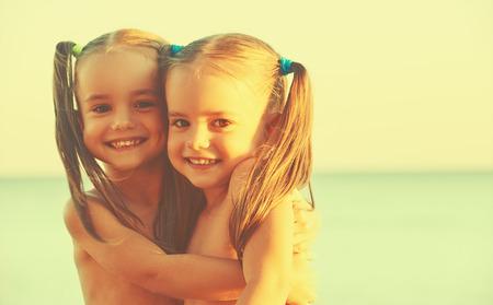 niños felices: felices los niños de la familia hermanas gemelas en la playa en el mar Foto de archivo