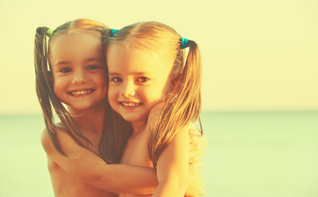 twin sister: happy family children twin sisters on the beach at Sea Stock Photo