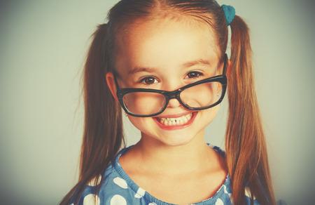 A funny smiling child girl in glasses Standard-Bild