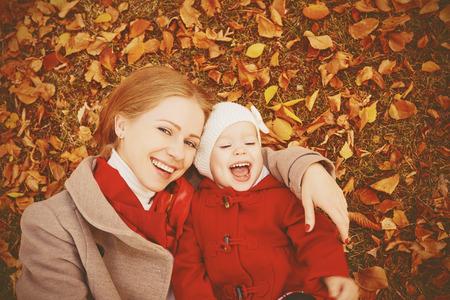 familia abrazo: familia feliz: la madre y la pequeña hija Juego de niños que abrazan en caminata del otoño en la naturaleza al aire libre