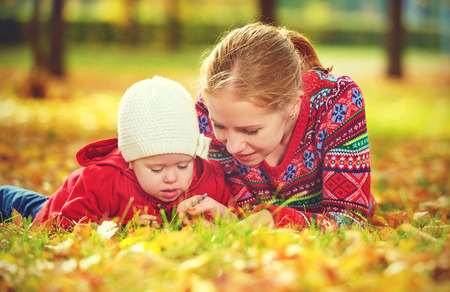 fall fun: happy family: mother and child little daughter play cuddling on autumn walk in nature outdoors