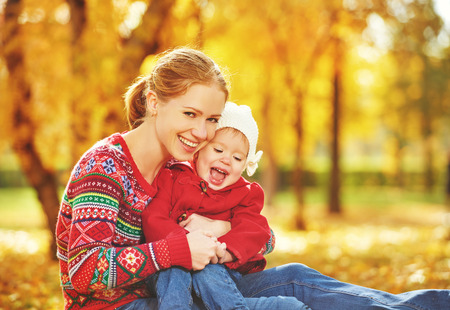 young leaves: happy family: mother and child little daughter play cuddling on autumn walk in nature outdoors