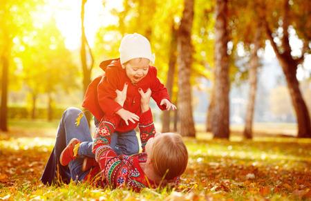 al aire libre: familia feliz: la madre y la pequeña hija Juego de niños que abrazan en caminata del otoño en la naturaleza al aire libre