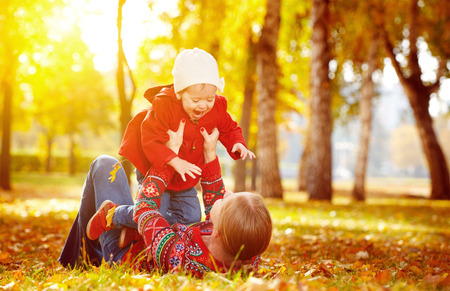outdoor: happy family: mother and child little daughter play cuddling on autumn walk in nature outdoors