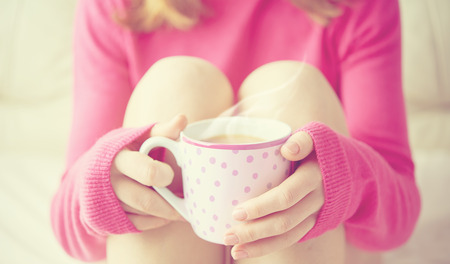 women holding cup: warm cup of hot coffee warming in the hands of a girl