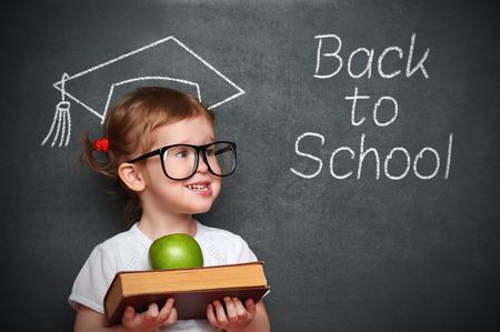 niño escuela: bastante pequeña colegiala muchacha con los libros y la manzana en una junta escolar Foto de archivo