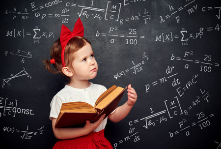 blank chalkboard: wunderkind little girl schoolgirl with a book from the blackboard with physical formulas