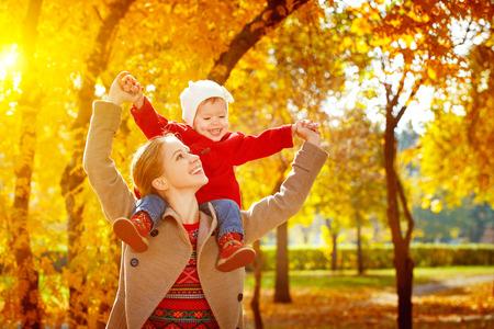 família: família feliz: mãe e filha pequena brincadeira que afaga na caminhada do outono na natureza ao ar livre