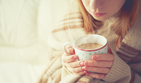 cold beverages: warm cup of hot coffee warming in the hands of a girl