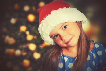 miracle tree: happy child girl in a Christmas hat waiting for a miracle