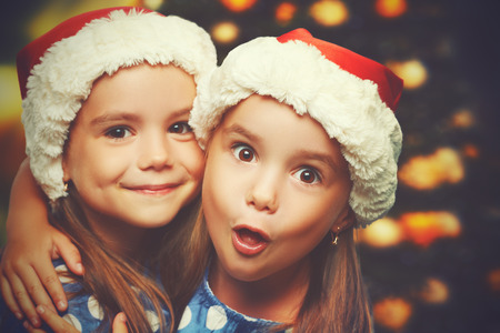 santa hat: Christmas Happy funny children twins sisters hugging