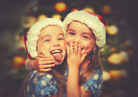gemelas: Feliz Navidad de los niños divertidos gemelos hermanas abrazan