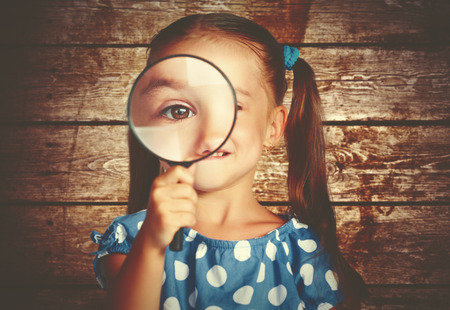 child girl playing with a magnifying glass in the detective Foto de archivo