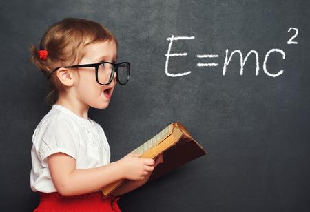 educação: wunderkind estudante pequena menina com um livro a partir do quadro-negro com fórmulas físicas Banco de Imagens