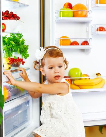 comidas saludables: niña feliz cerca de la nevera con alimentos saludables, frutas y verduras Foto de archivo