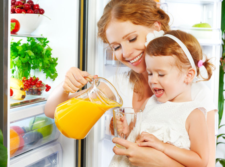 refrigerator kitchen: happy family mother and baby daughter drinking orange juice in the kitchen near the refrigerator Stock Photo