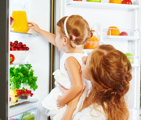 juice glass: happy family mother and baby daughter drinking orange juice in the kitchen near the refrigerator Stock Photo