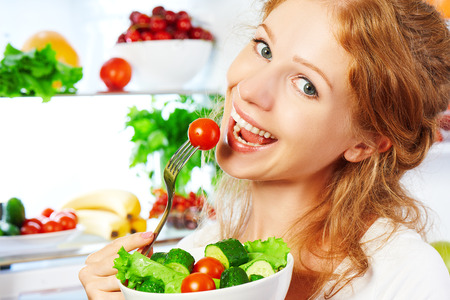 happy woman eats healthy food vegetable vegetarian salad about refrigerator Banco de Imagens