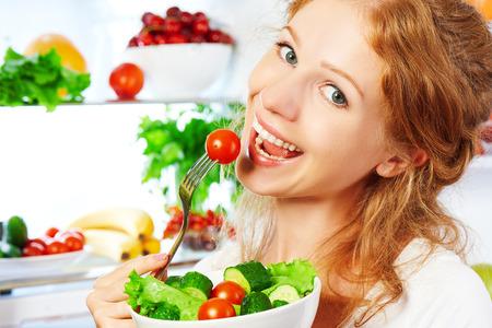 alimentos saludables: mujer feliz come sano alimentos vegetales Ensalada vegetariana acerca refrigerador Foto de archivo