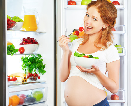 pregnant: Happy pregnant woman eating salad near refrigerator at home