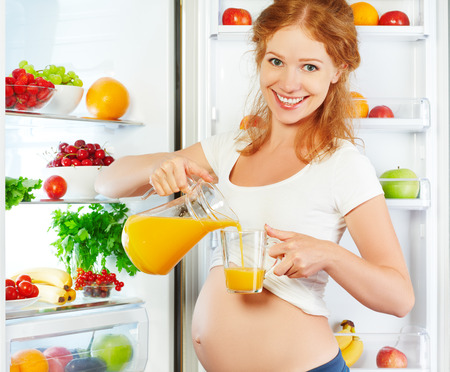 woman eating fruit: nutrition and diet during pregnancy. Pregnant woman standing near refrigerator with with orange juise