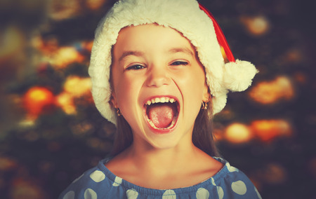 surprise face: happy child girl in a Christmas hat waiting for a miracle
