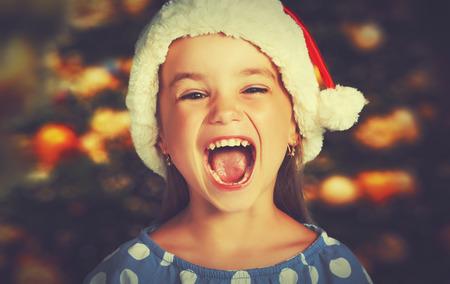 sorpresa: niña feliz en un sombrero de la Navidad a la espera de un milagro
