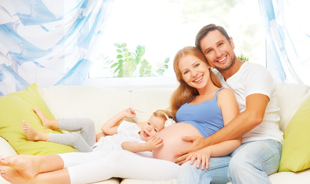 happy family. pregnant mother, father, and child daughter on sofa at home